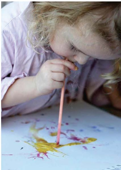 child blowing paint